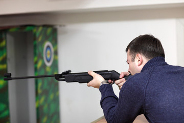 Man is aiming by air rifle