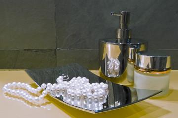 collana di perle sul piatto di acciaio sul piano del bagno