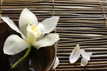 Photo sur Aluminium Spa bowl of orchid, petal on bamboo mat