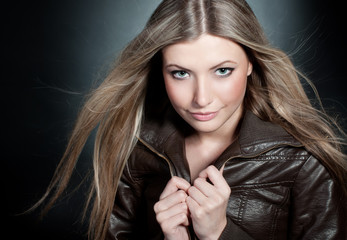 Beautiful blond girl on the black background with blowing hair