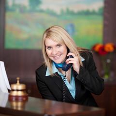 lächelnde hotelangestellte am telefon