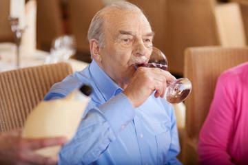älterer mann trinkt wein im restaurant