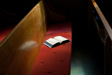 Open Bible Lying on Church Pew in Narrow Sunlight Band