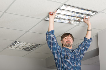 Electrician installs lighting to the ceiling.