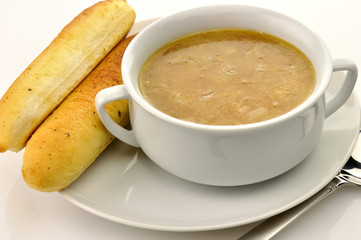 French Onion Soup in a white bowl with bread sticks
