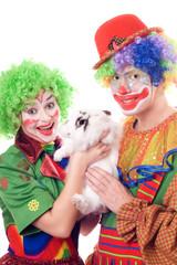 Two joyful clown with a white rabbit