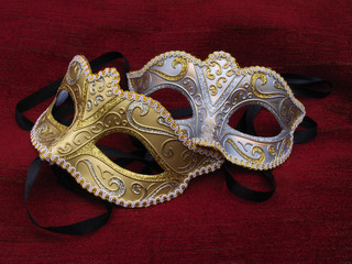 Two masquerade mask on red cusion