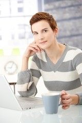 Young woman with coffee mug and laptop