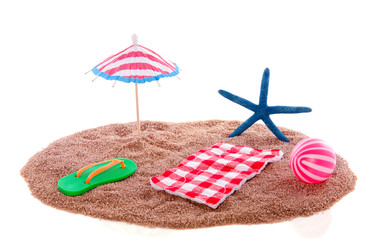 A parasol with a towel and beach equipment in the sand isolated