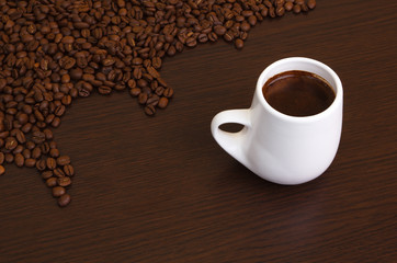 Coffee grains with a white cup on a brown background