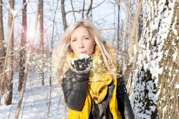 Winterwald Blonde Frau pustet Schnee