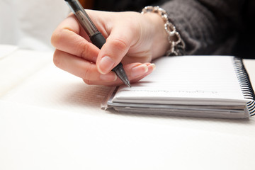 Woman hand writing on a notepad