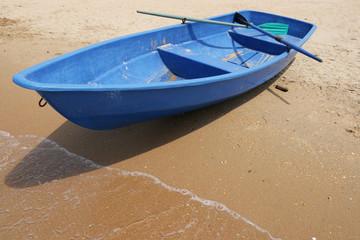 Dark blue boat on a sandy beach