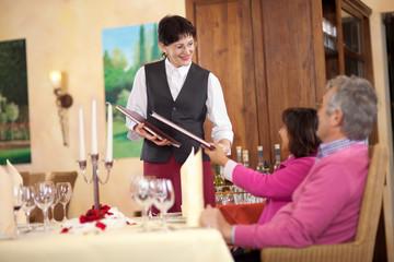 kellnerin überreicht gästen die speisekarte