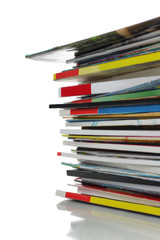 stack of colorful magazine over white background