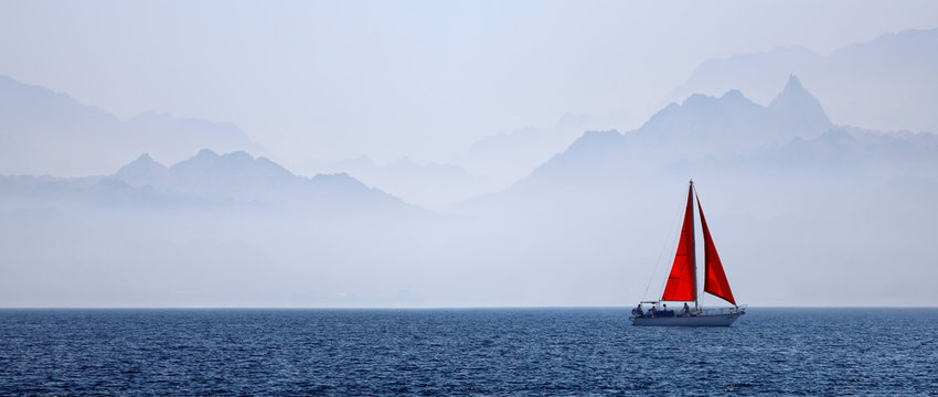 Yacht with a red sail on a mountain background
