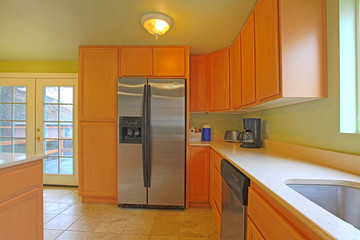 Green and orange kitchen with black refrigerator