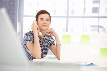 Smiling office worker on landline call