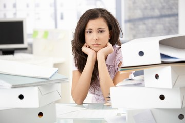 Young office worker sitting troubled in office