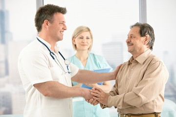 Doctor shaking hands with senior patient
