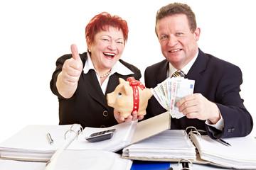 Senioren halten Geld und Sparschwein