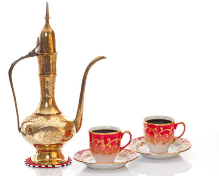 Arabic brass coffee pot with a welcoming  cups full of coffee.