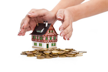 Womens hands protect miniature house with the coins. Focus on co