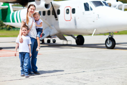 Mother and kids in front of airplane
