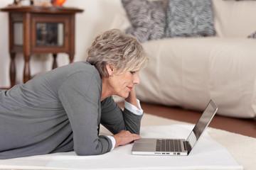 moderne seniorin mit notebook im wohnzimmer