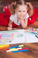 The girl draws on a floor