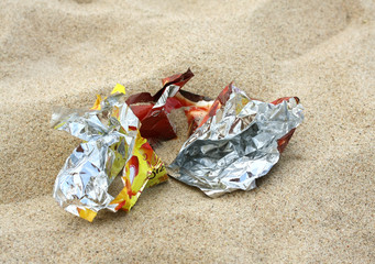 Crumpled foil package on the beach