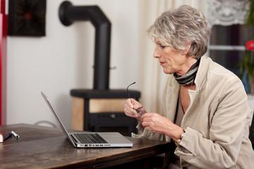 ältere frau mit laptop im wohnzimmer