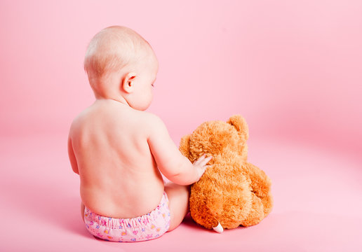 The small child with a bear cub on a pink background