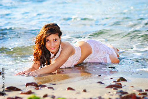 Young woman lying on beach sun tanning