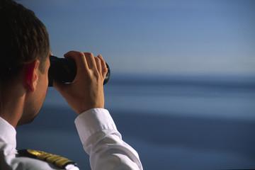 Offizier schaut mit dem Fernglas übers Meer