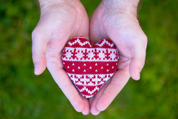.man hands with red knitted heart
