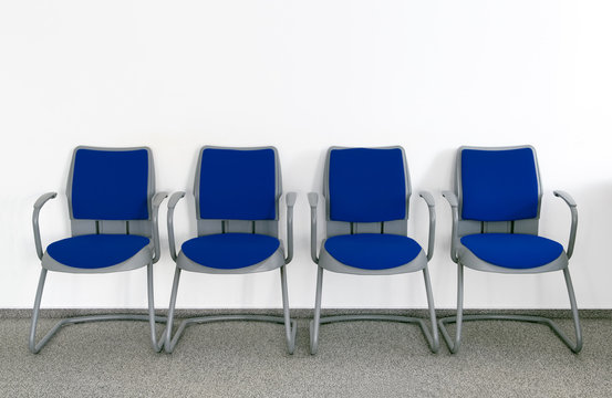 Four Blue chairs in simple empty waiting room
