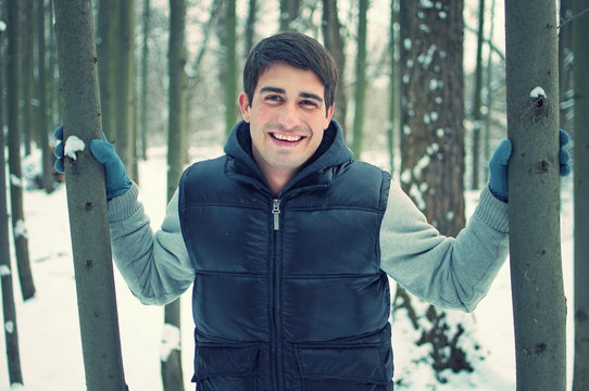 Fashion portrait of smiling handsome young man holding trees in