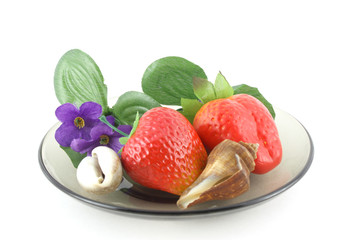 Artificial flowers, strawberries and sea shells on saucer.