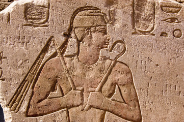 Ancient Egyptian carving of Pharaoh with flail and sceptre