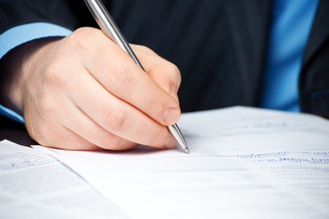 closeup of businessman`s hand signing contract