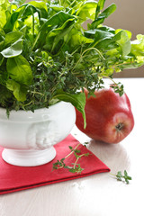 Green salad in a white porcelain bowl and red apple