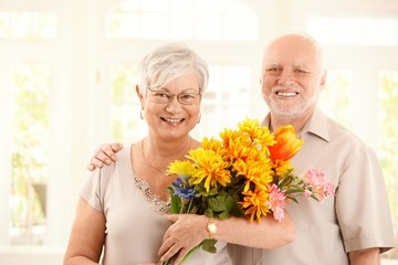 Portrait of happy elderly couple with flowers