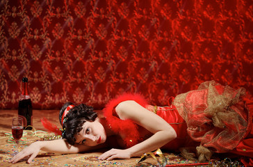 Lady in red dress lies on the parquet, covered the confetti