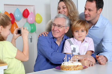 Little girl taking picture of family on birthday celebration