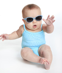 Baby girl wearing a blue swimsuit and sunglasses