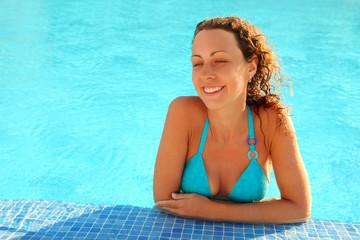 Smiling girl in blue bikini stands in swimming pool