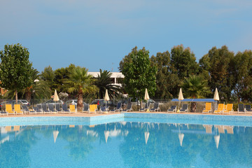 Big blue pool, yellow loungers and white parasol