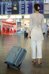 young woman standing in hall of airport with luggage