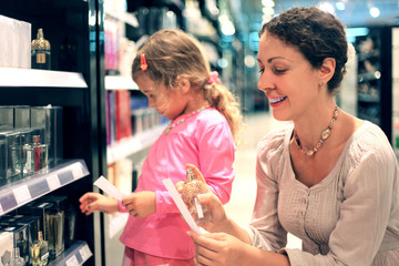 mother and little daughter choose perfume in perfume shop,